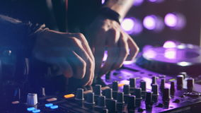 Close-up. Hands of DJ tweak various track controls on DJ mixer console at nightclub party. stock video footage
