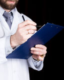 Close-up hands of a doctor, he takes notes in a patient's medical history Stock Photography