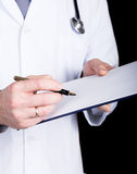 Close-up hands of a doctor, he takes notes in a patient's medical history Stock Photos