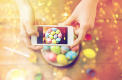 Close up of hands with easter eggs and smartphone Stock Photography
