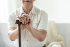 Close-up of hands of an elderly man holding onto a cane stock images