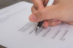 Close up of hands employment application form, please write with a pen. Stock Image