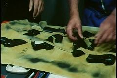 Close-up hands examining different guns laid out on cloth