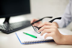 Close up of hands with eyeglasses and notebook Royalty Free Stock Image