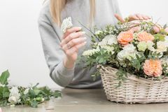 Close-up hands female florist. Floral workshop - woman making a beautiful flower composition a bouquet in a wicker royalty free stock photos