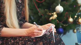 Close up hands of female writing letter on knees at Christmas Eve. Close up hands of female writing letter at Christmas Eve. Woman is sitting near decorated stock video