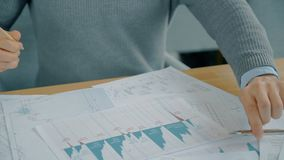 Close up hands of financial analytic working on graphs in the office. Concept of: business peope, modern office, charts and graphs, financial planning, paper stock footage