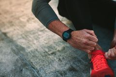 Top view of a man tying shoe lace. Close up of hands of a fitness man wearing a digital wrist watch tying shoe laces. Cropped shot of a man wearing shoes for royalty free stock images