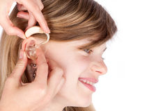 Close up of hands fitting a hearing aid to a happy young girl. I. Solate on white Royalty Free Stock Image