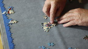 Close up hands fitting jigsaw puzzle pieces. stock video footage
