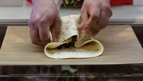 Folding a traditional mexican burrito with cochinita pibil corn and chili jalapeños. Close up on hands folding a traditional mexican burrito with cochinita stock video