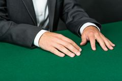 Close up of hands of gambler sitting at the table Stock Image