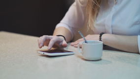 Close up of hands of girl with mobile phone in cafe with cup of coffee on the table. stock video footage