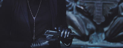 Close-up hands of girls in black leather gloves, grip gun Stock Photo