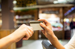 Close up of hands giving credit card in mall Royalty Free Stock Photos