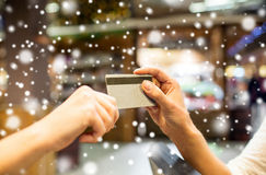 Close up of hands giving credit card in mall. Sale, shopping, payment, consumerism and people concept - close up of hands giving credit card at checkout in Royalty Free Stock Photo