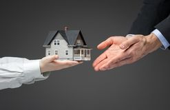 Close up of hands giving home model to other hands Royalty Free Stock Image