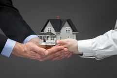 Close up of hands giving house model to other hands Stock Image