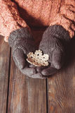 Close-up hands in glove. Hands in a grey gloves holding white knitted snowflake on a wooden background Stock Images
