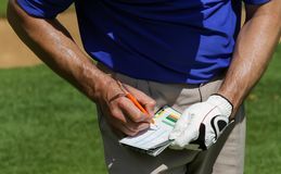 Golfer keeping score on scorecard. Close up of hands of a Golfer keeping score on scorecard Royalty Free Stock Photography
