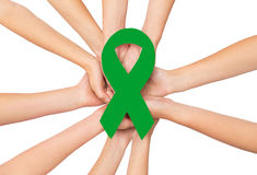 Close up of hands with green awareness ribbon. Healthcare, charity, people and medicine concept - close up of hands with green organ transplant awareness ribbon Royalty Free Stock Images