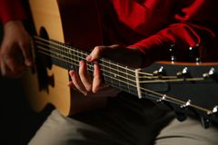 Close-up hands with guitar. On dark stock image
