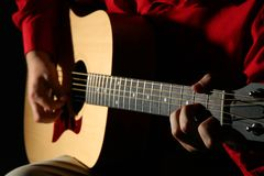 Close-up hands with guitar. On dark stock images