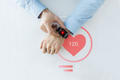 Close up of hands with heart icon on smart watch Stock Photo