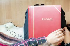Close up hands hold and open red family photo album sitting at home, past memory concept f stock photography