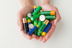 Close up of hands holding alkaline batteries heap Royalty Free Stock Photography