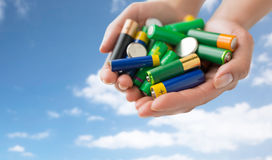 Close up of hands holding alkaline batteries heap Royalty Free Stock Photos