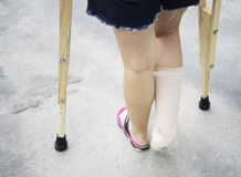 Close up of hands holding crutches waking on the street royalty free stock photography