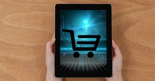 Close-up of hands holding digital tablet with shopping cart icon on screen Stock Photography