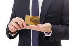 Close up of hands holding gold card on white background. stock image