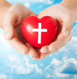 Close up of hands holding heart with cross symbol Stock Image