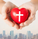 Close up of hands holding heart with cross symbol Stock Photo