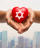 Close up of hands holding heart with jewish star. Religion, christianity, jewish cummunity and charity concept - close up of female hands holding red heart with Royalty Free Stock Images