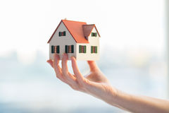 Close up of hands holding house or home model Stock Photos