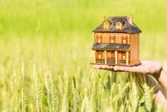 Close-up of hands holding a house model on a green meadow background. royalty free stock photography