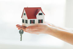 Close up of hands holding house model and keys Stock Photo