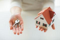 Close up of hands holding house model and keys Royalty Free Stock Photography