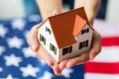 Close up of hands holding house over american flag stock photography