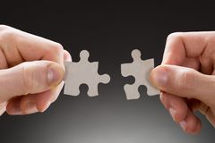 Close-up of hands holding jigsaw pieces. On Grey Background Stock Image