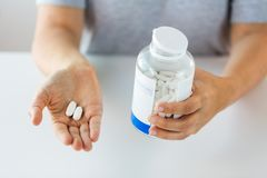 Close up of hands holding medicine pills and jar Royalty Free Stock Images