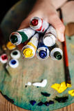 Close up of hands holding oil paints, palette background. Stock Images