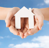 Close up of hands holding paper house. People, home, real estate and mortgage concept - close up of hands holding paper house Stock Photo