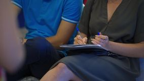 Close-up of Hands holding pens and making notes at the conference stock video footage