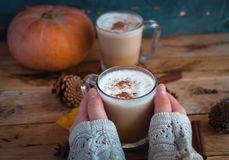 Close-up of hands holding pumpkin spice latte in glass cup, on wooden background royalty free stock photography