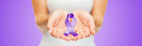 Close up of hands holding purple awareness ribbon. Healthcare and social problems concept - close up of woman hands holding purple domestic violence awareness Stock Images