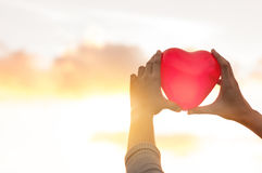 Close up hands holding red heart over cloudy sky with sunlight stock images